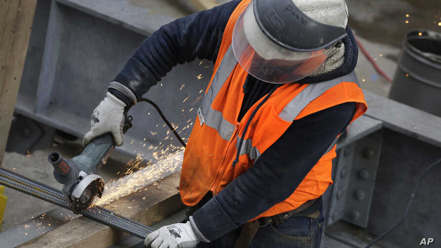 FILE - Sparks fly as a construction worker uses a grinder to cut through steel reinforcing bars in New York, Feb. 1, 2016.