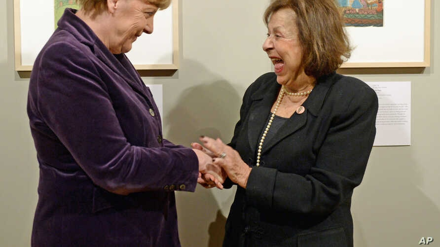 "Artist Nelly Toll (r) shares a light moment with German Chancellor Angela Merkel as Merkel inaugurates the exhibition ""Art from the Holocaust - 100 works from the Yad Vashem collection"" in the German Historical Museum in Berlin, Jan. 25, 2016."