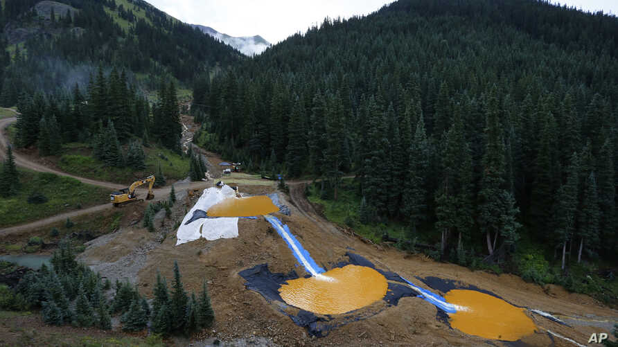 FILE - Water flows through a series of retention ponds built to contain and filter out heavy metals and chemicals from the Gold King mine chemical accident, in the spillway about 1/4 mile downstream from the mine, outside Silverton, Colorado, Aug. 12