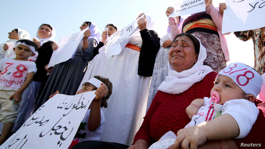 Yazidi women cry as they attend a demonstration at a refugee camp in Kurdish-dominated city of Diyarbakir, Turkey, to mark the second anniversary of what a U.N.-appointed commission of independent war crimes investigators termed a genocide against th