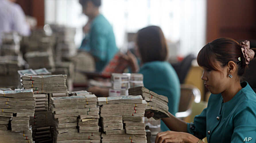 Workers count Burma's kyat banknotes at the office of a local bank in Rangoon, April 2, 2012.