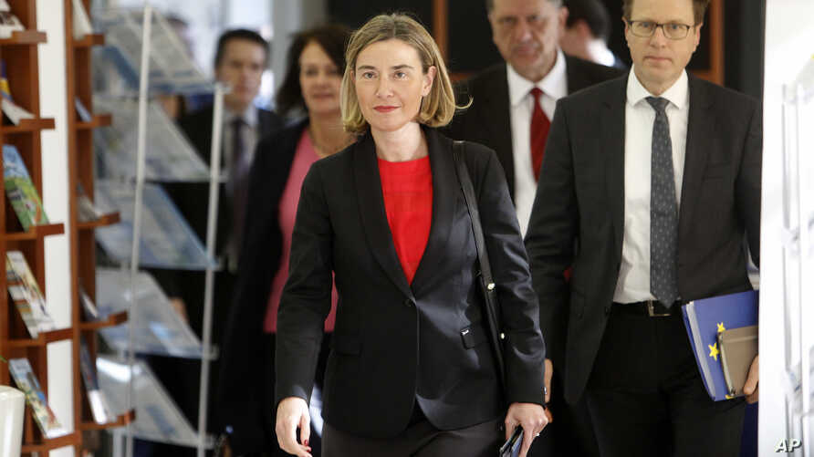 Federica Mogherini, center, the European Commission's high representative for foreign affairs and security policy, accompanied by EU Ambassador to Macedonia Samuel Zbogar, right, arrives at the European Union office in Skopje, Macedonia, March 2, 201