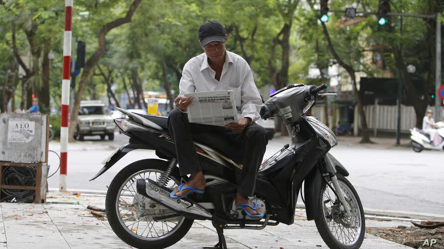 Nguyen Kim Lan reads a newspaper as he waits for customers at an intersection in Hanoi, Vietnam, June 21, 2017. Lan, 62-year-old traditional motorbike taxi driver, or Xe Om, used to make a decent living shuttling customers, but his clientele has dwin