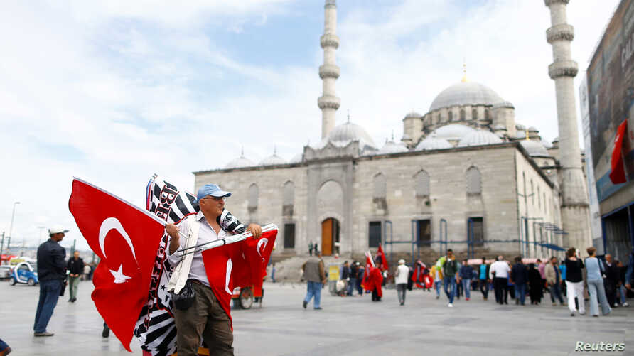 A flag seller waits for customers in front of the 17th century Ottoman era New Mosque (Yeni cami) in Istanbul, Turkey, May 4, 2016.