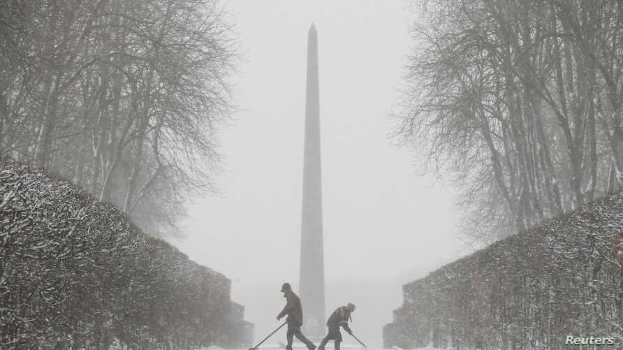 Workers remove snow during a heavy snowfall in Kyiv, Ukraine, Dec. 18, 2017.