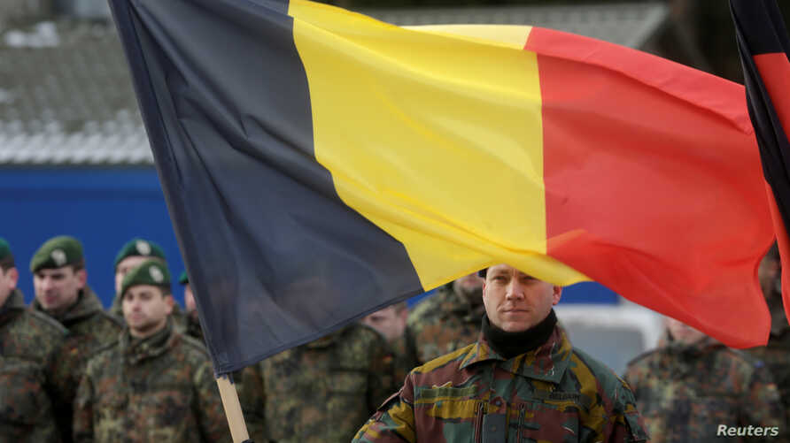 A Belgian soldier holds his national flag during a ceremony to welcome the German battalion being deployed to Lithuania as part of NATO deterrence measures against Russia in Rukla, Lithuania, Feb. 7, 2017.