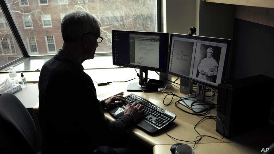 Brown University professor David Kertzer sorts through documents on his computer, including a photo of Pope Pius IX, in his office on the Brown campus in Providence, April 17, 2018.