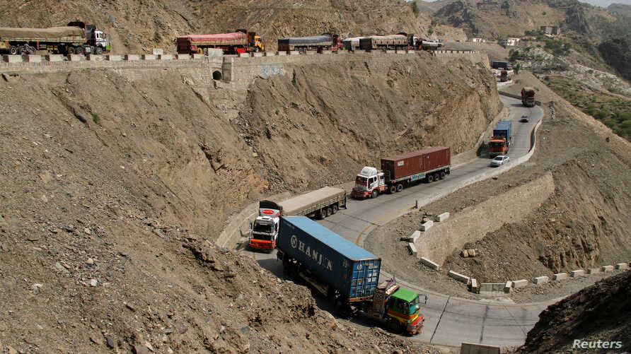 Trucks, stuck for days in Pakistan due to border conflict, travel toward the border post at Torkham, Pakistan June 18, 2016.