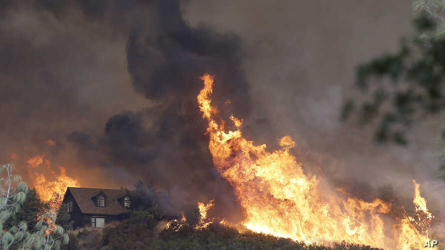 Fires approach a home near Lower Lake, Calif., July 31, 2015. A series of wildfires were intensified by dry vegetation, triple-digit temperatures and gusting winds.