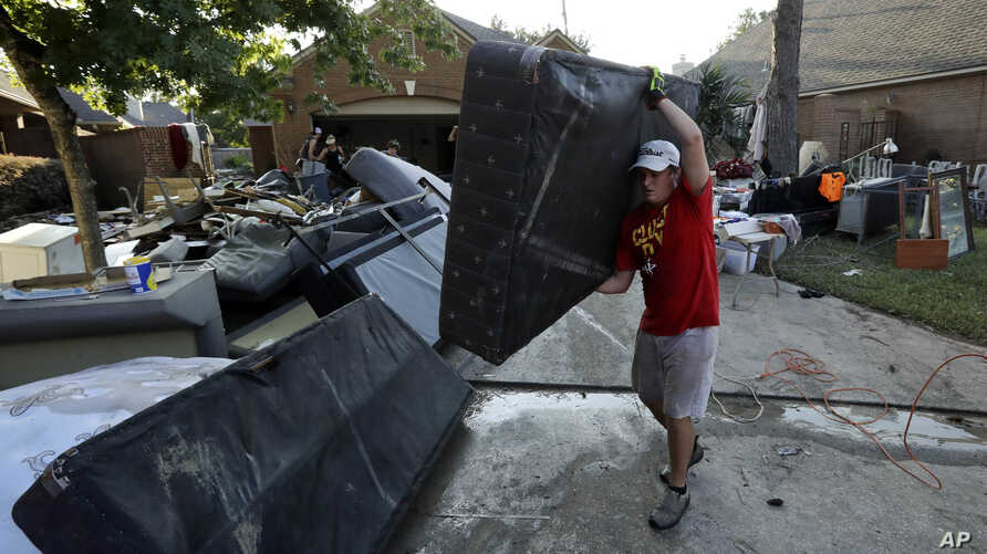 Tyler Moody removes a mattress from a friend's home after floodwaters from Tropical Storm Harvey drenched the city, Aug. 31, 2017, in Houston.