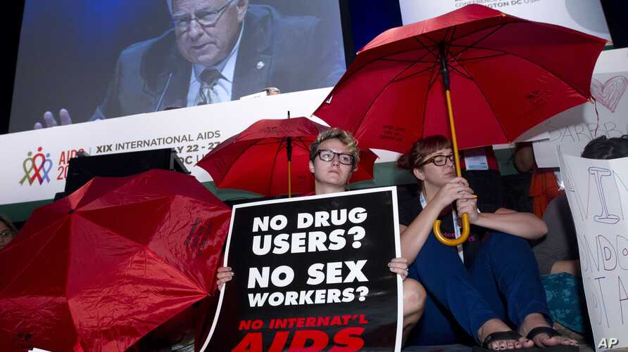 People protest in front of the stage as Sen. Mike Enzi is seen on a giant video screen during the XIX International AIDS Conference in Washington, July 25, 2012.