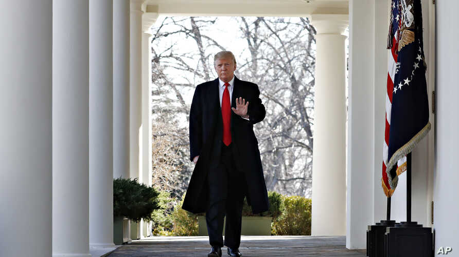 FILE - President Donald Trump waves as he walks through the Colonnade from the Oval Office of the White House on arrival to make an announcement.
