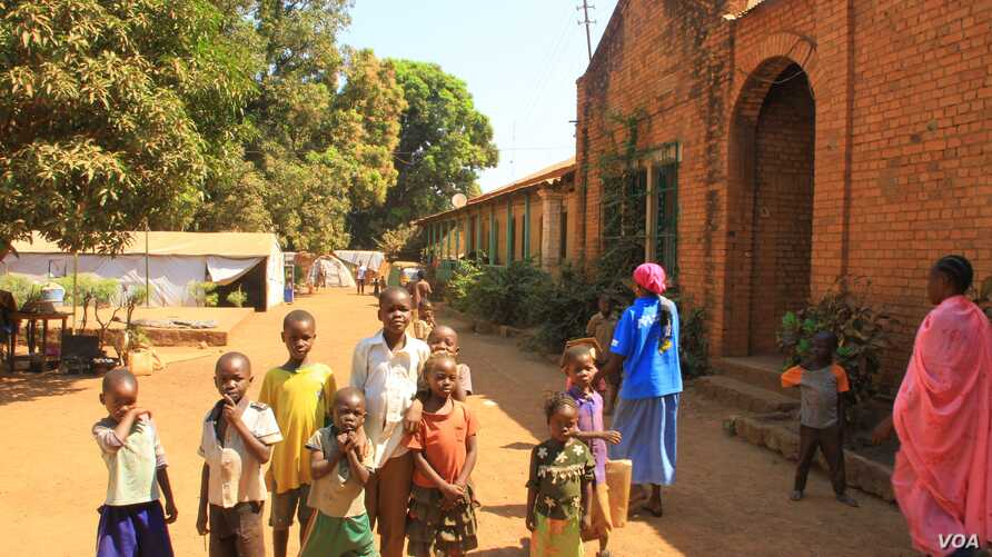 Young IDPs play in front of church buildings at the St. Mary Help of Christians Cathedral in Wau, Western Bahr el Ghazal, Dec. 8, 2016. (VOA/Jill Craig)