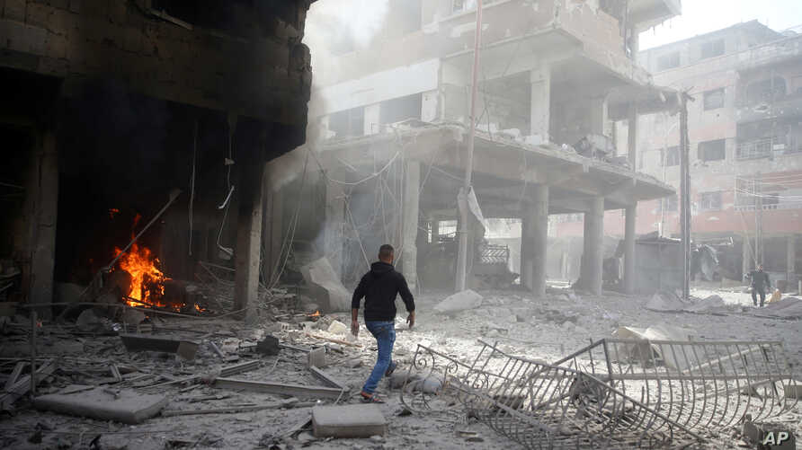 A man walks on rubble at a damaged site after an airstrike in the besieged town of Douma, Eastern Ghouta, Damascus, Syria, Feb. 9, 2018.