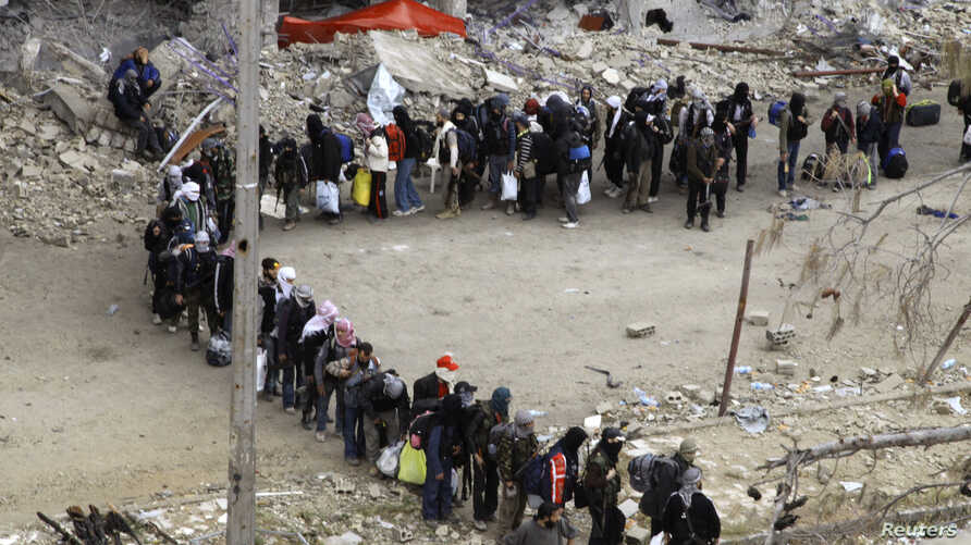 Rebel fighters queue as they wait to be evacuated from the Old City of Homs, May 8, 2014.