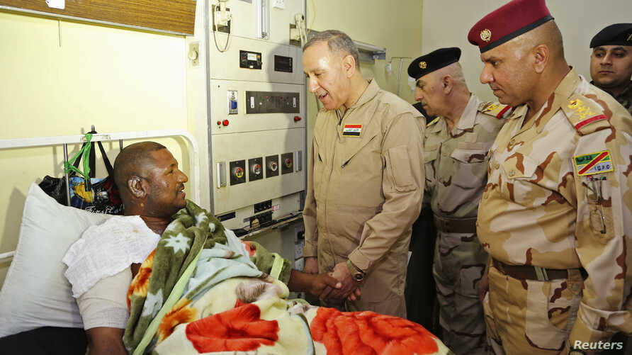 Iraqi Defense Minister Khaled al-Obeidi talks to a soldier wounded in the battle for Baiji during a hospital visit in Baghdad, Nov. 15, 2014.