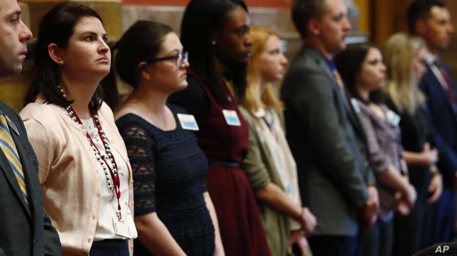 Legislative aides stand in unison during the reading of a Democratic resolution calling for the expulsion of Colorado state Sen. Randy Baumgardner, R-Hot Sulphur Springs, during a debate on the chamber's floor April 2, 2018.