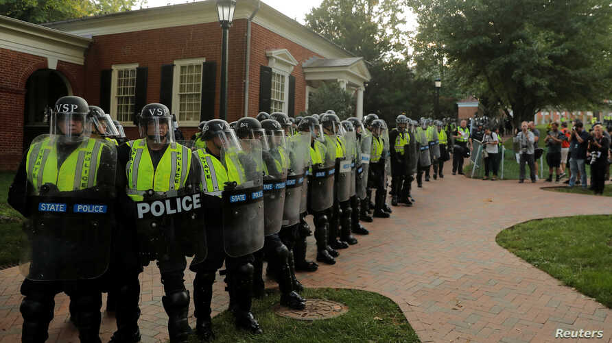"""Virginia State Police officers form a cordon at the University of Virginia ahead of the one year anniversary of the 2017 Charlottesville """"Unite the Right"""" protests, in Charlottesville, Va., Aug. 11, 2018."""