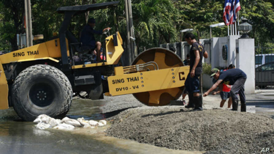 Workers fix the entrance to an air force cadet school near Don Muang airport as flood waters approach Tuesday, Oct. 25, 2011 in Bangkok, Thailand.