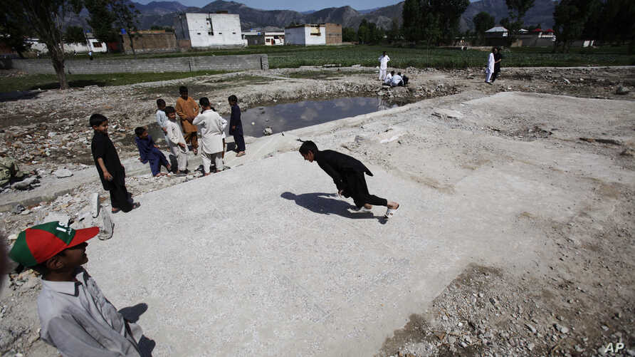 Pakistani boys play at the demolished compound of Osama bin Laden, in Abbottabad, Pakistan, May 2, 2012.