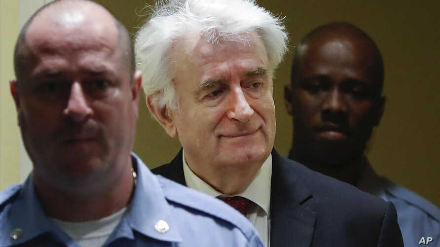 Former Bosnian Serb leader Radovan Karadzic, center, arrives to open his appeal at a U.N. court against his convictions on charges including genocide and crimes against humanity and his 40-year prison sentence in The Hague, Netherlands, April 23, 201