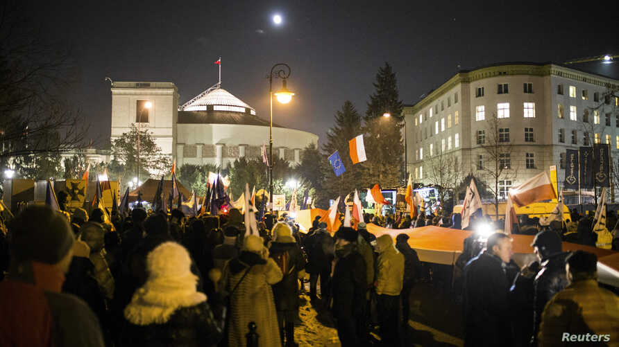 Demonstrators wave Polish and European Union flags during a protest outside the Parliament building in Warsaw, Jan. 11, 2017.