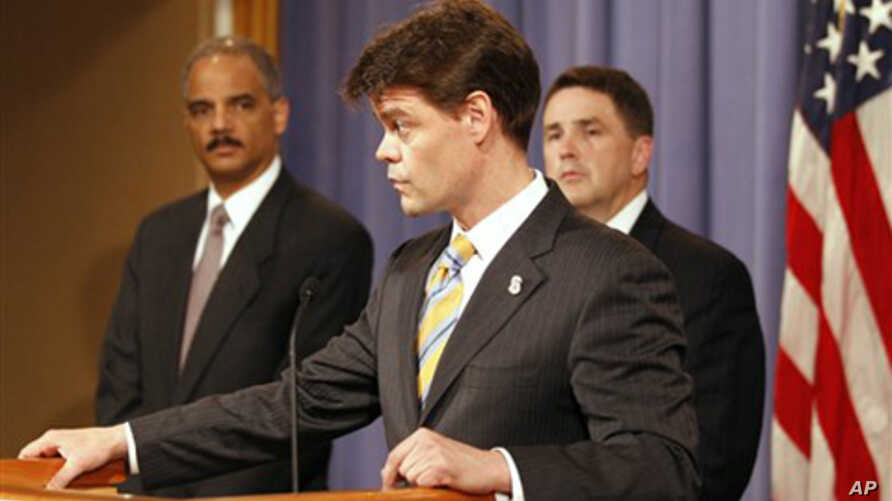 Attorney General Eric Holder, left, listens as U.S. Immigration and Customs Enforcement Assistant Secretary John Morton speaks during a news conference at the Justice Department in Washington, 10 June 2010