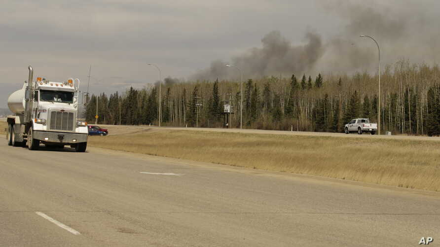 A truck drives by smoke from a wildfire near Fort McMurray, Alberta on Sunday, May 8, 2016.