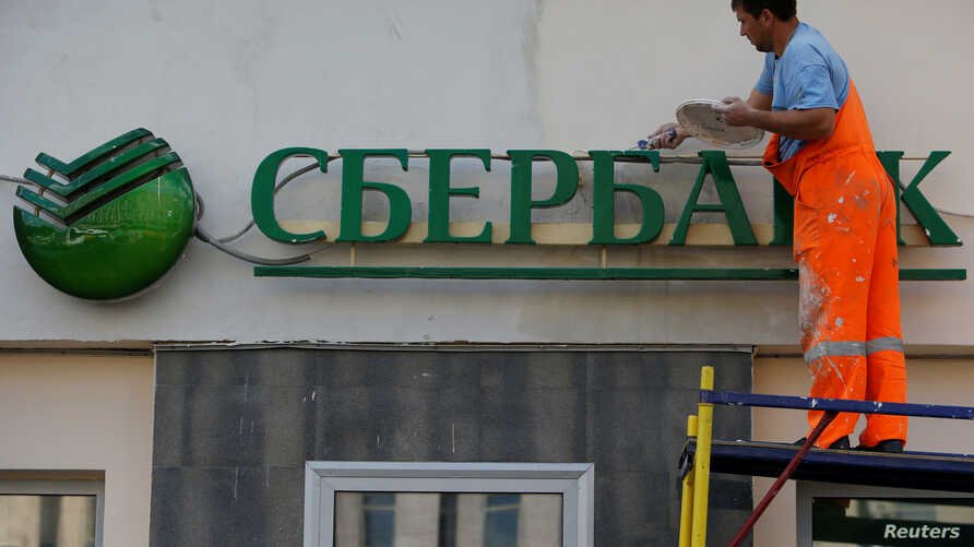 A worker paints the facade of a branch of Sberbank in central Moscow, Russia, Aug. 17, 2016.