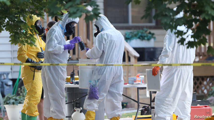 """FILE - FBI and law enforcement officers in hazardous material suits prepare to enter a house, with the FBI says """"potentially hazardous chemicals"""" in Logan, Utah, Oct. 3, 2018."""