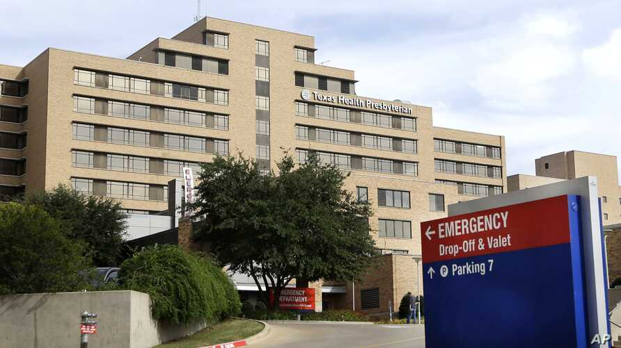 FILE - A sign points to the entrance to the emergency room at Texas Health Presbyterian Hospital Dallas, where U.S. Ebola patient Thomas Eric Duncan was being treated and two health care workers contracted the disease, in Dallas.