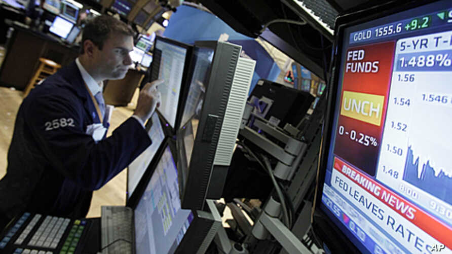 A television monitor shows the interest rate decision of the Federal Reserve as specialist Philip Finale works on the floor of the New York Stock Exchange, June 22, 2011.