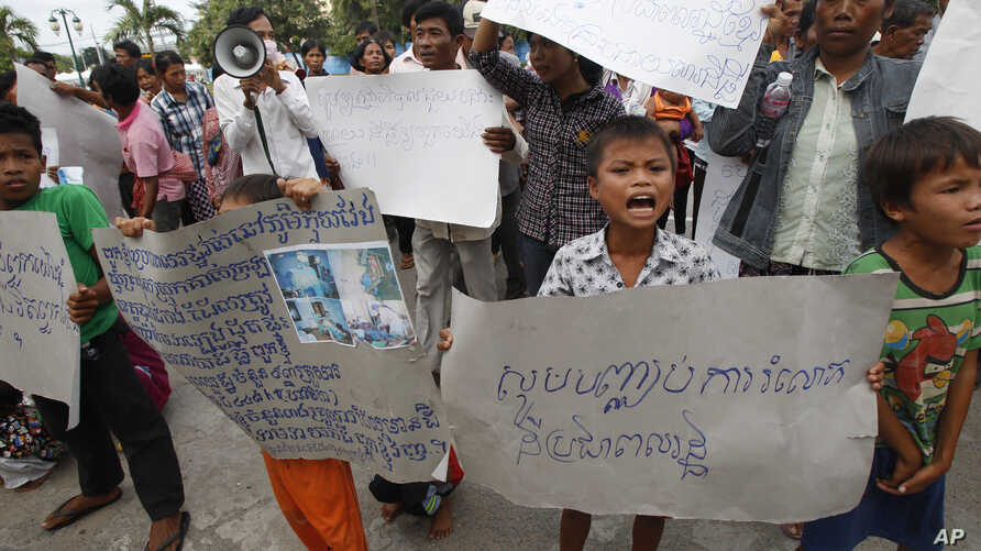 """FILE - A boy holds a banner reading """"Please stop grabbing our land"""" at a rally by land evection victims in front of the National Assembly in Phnom Penh, Cambodia, Sept. 1, 2014."""