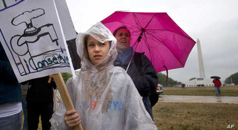 In a steady rain storm near the Washington Monument, Anastasia Bardin, 10, of New York City, left, with her mother Lyn Bardin, rallies with the Earth Action Team as part of Earth Day activities on the National Mall in Washington Sunday, April 22, 201
