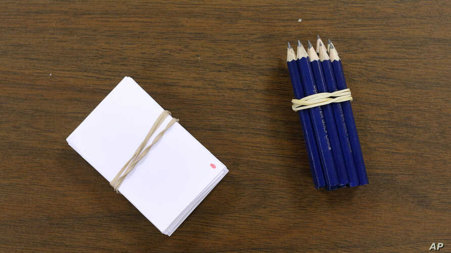 Slips of paper and pencils to be used by voters to select their candidates sit on a table before a Republican party caucus in Nevada, Iowa, Feb. 1, 2016.