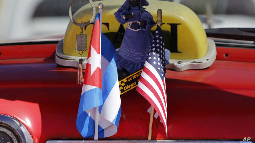 The stars and stripes and the Cuban national flag are placed together on the dashboard of a vintage American convertible in Havana, Cuba, Feb. 18, 2016.