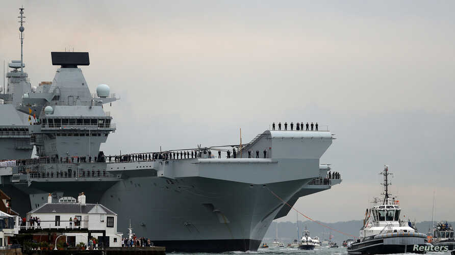 The Royal Navy's new aircraft carrier, HMS Queen Elizabeth, is towed by tugs as it arrives at Portsmouth Naval base, its new home port, in Portsmouth, Britain, Aug. 16, 2017.