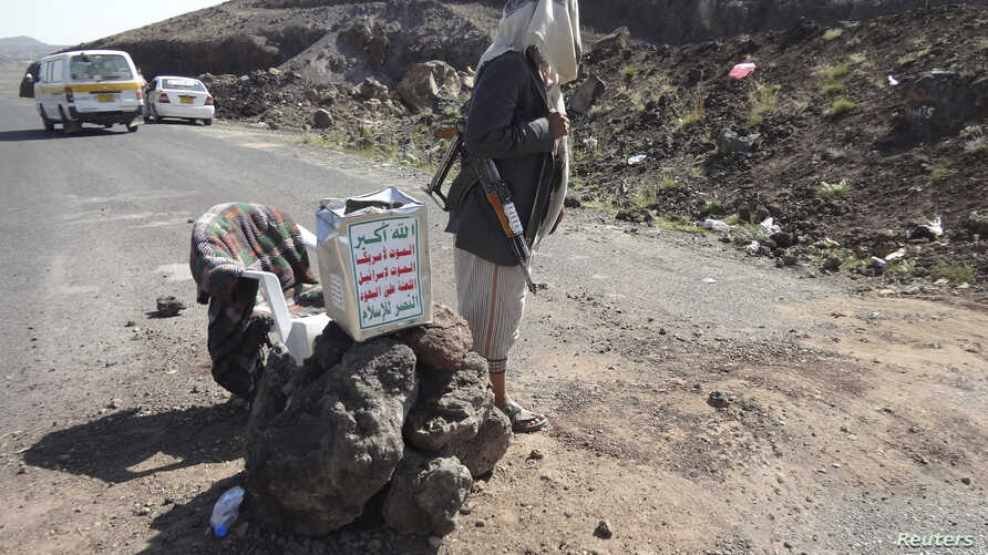 A Shi'ite militant mans a checkpoint on a road in Yemen's northwestern province of Omran, June 3, 2014.