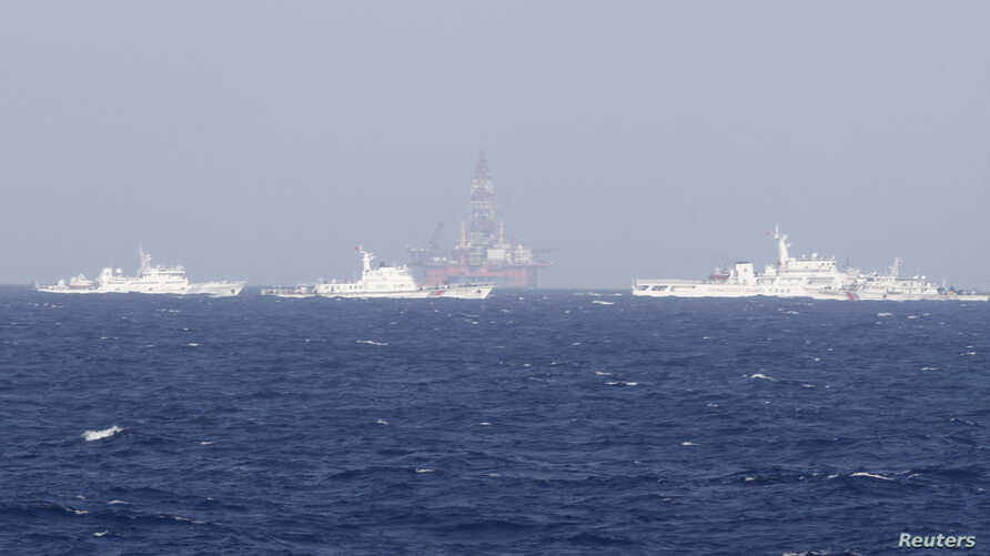 FILE - Chinese oil rig Haiyang Shi You 981 is seen surrounded by ships of China Coast Guard in the South China Sea, about 210 km (130 miles) off shore of Vietnam.