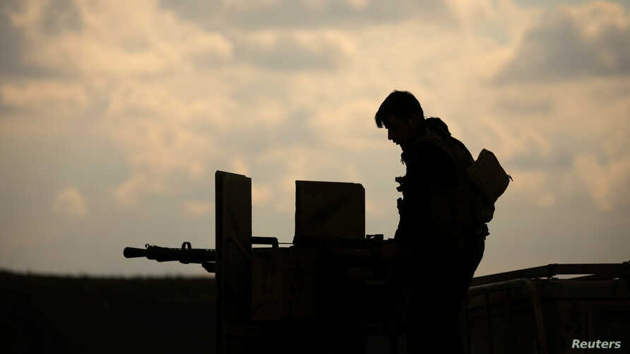 A member of Syrian Democratic Forces (SDF) stands on a pick up truck mounted with a weapon near Baghouz, Deir Al Zor province, Syria February 11, 2019.