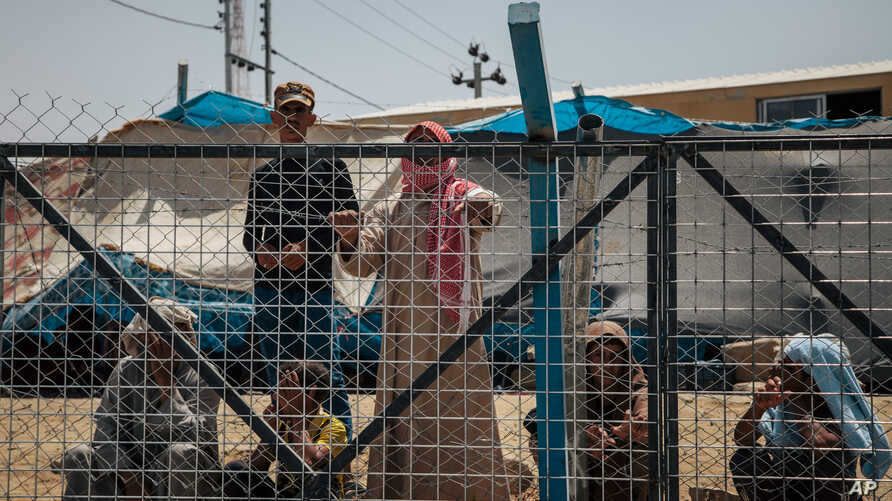Mideast Iraq Faltering IS: In this August 17, 2016 photo, men wait behind a fenced area where they are interrogated before being allowed to stay, at the Dibaga Camp for displaced people, in Hajj Ali, northern Iraq.