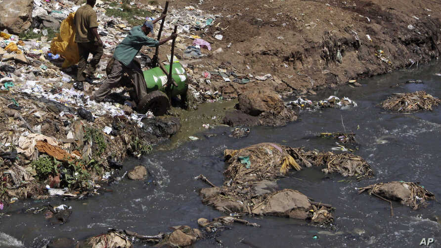 FILE - Workers dump effluent from pit latrines from the Korogocho slum of Nairobi, Kenya into a local water course.