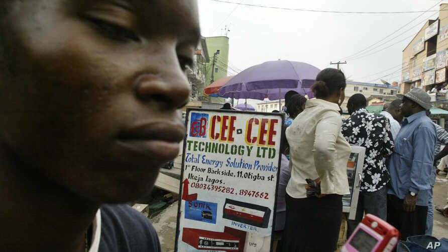 Andrew Owoyemi  buys a telephone hand-set at the computer village in Lagos, Nigeria, March 2006.