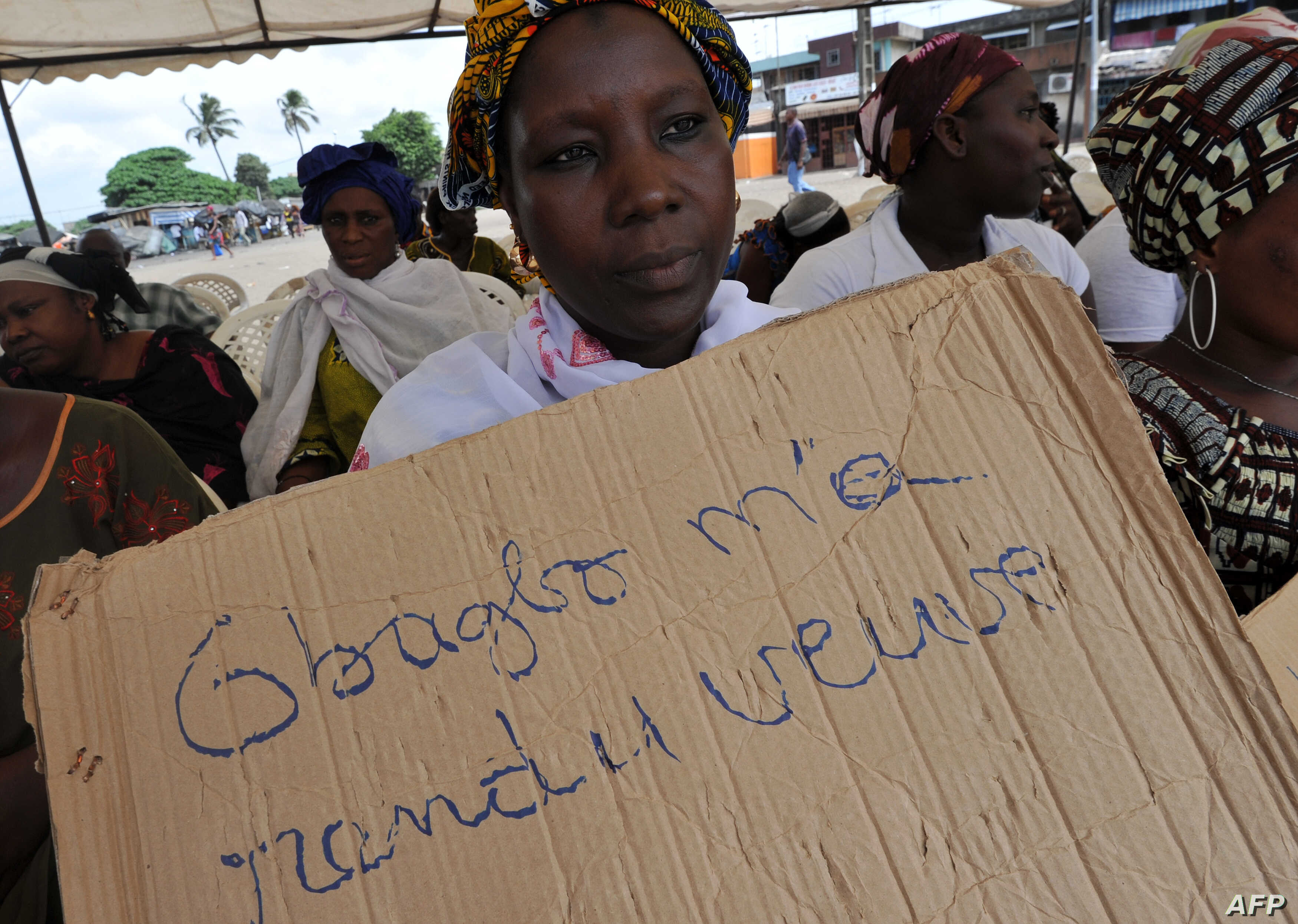 """A victim of the 2010 post-election crisis hold a placard reading """"Gbagbo turned me into a widow"""" during a gathering in the Kouassai popular district of Abidjan, Feb. 28, 2013."""