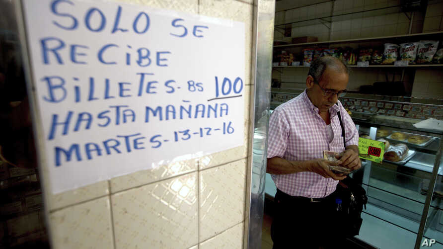 """A man counts his 100-bolivar notes next to a sign alerting customers with a message in Spanish that reads: """"100-bolivar notes will only be received until Tuesday, 12-13-16,"""" inside a bakery in downtown Caracas, Venezuela, Dec. 12, 2016."""
