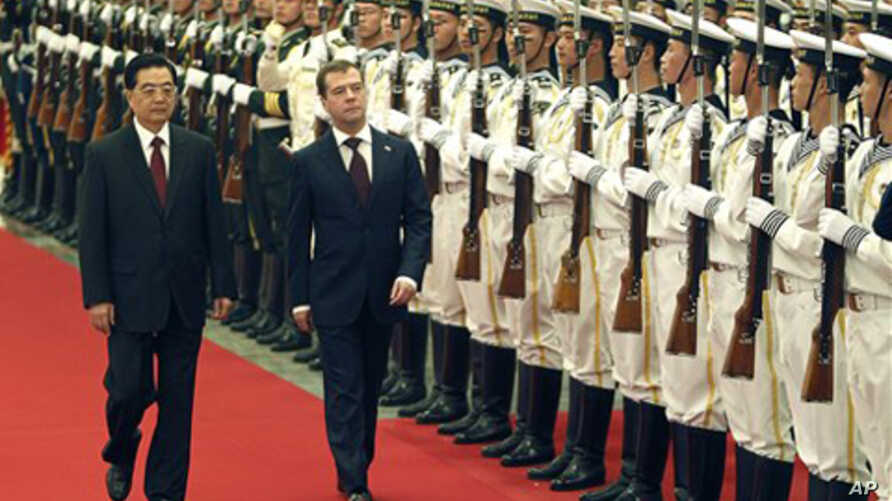 Russian President Dmitry Medvedev, center, with his Chinese counterpart Hu Jintao inspects a guard of honor during a welcoming ceremony at the Great Hall of the People in Beijing Monday, Sept. 27, 2010