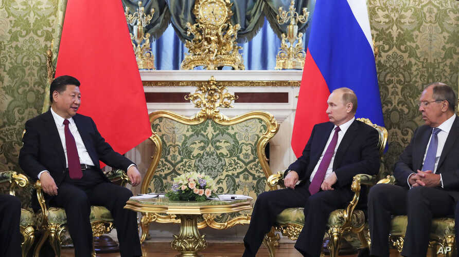 Russian President Vladimir Putin, second right, meets with Chinese President Xi Jinping, left, during a meeting in the Kremlin, in Moscow, July 4, 2017. Russian Foreign Minister Sergey Lavrov is at right.