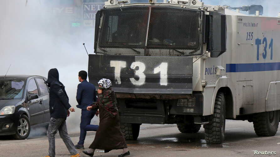 People walk past an armored police vehicle as Turkish riot police use tear gas to disperse Kurdish demonstrators during a protest against a curfew in Sur district and security operations in the region, in the southeastern city of Diyarbakir, Turkey,