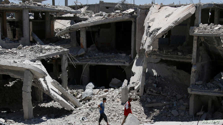 People walk amidst the rubble of damaged buildings in Deraa, Syria, July 15, 2017.