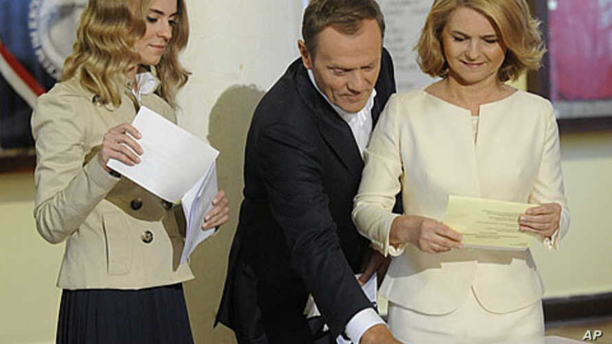 Polish Prime Minister Donald Tusk, center, his wife Malgorzata, right, and daughter, Katarzyna, cast their ballots during parliamentary elections in Warsaw, Poland, Sunday, October 9, 2011.
